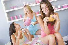 Stock Photo of Three young woman sitting at a table having tea and a snack