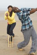 young couple playing cricket on autumn beach holiday - stock photo