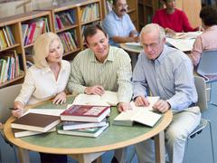 Three people in library with notepads (selective focus) - stock photo