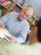Two men in library with notepads talking (selective focus) - stock photo