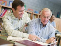 Two men in library talking (selective focus) - stock photo