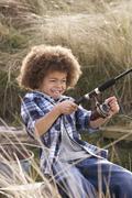 young boy fishing at seaside - stock photo