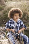 Young boy fishing at seaside Stock Photos