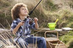 Young boy fishing at seaside Stock Photos