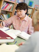 Man and woman sitting in library reading books (selective focus) Stock Photos