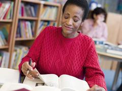 Woman sitting in library with a book and notepad (selective focus) Stock Photos