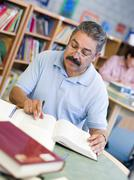Man sitting in library with a book and notepad (selective focus) - stock photo