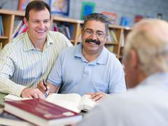 Two men sitting in library near another man with a book and notepad (selective Stock Photos