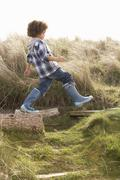 young boy going for walk in wellington boots - stock photo