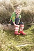 young girl putting on wellington boots - stock photo