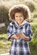 young boy holding worm outdoors - stock photo