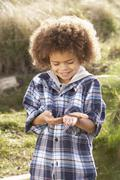 Young boy holding worm outdoors Stock Photos