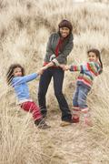 Stock Photo of mother and daughters having fun in sand dunes