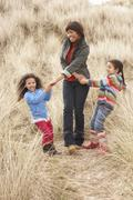 Mother and daughters having fun in sand dunes Stock Photos