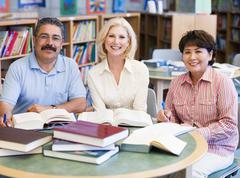 Stock Photo of Three people sitting in library with books and notepads (selective focus)