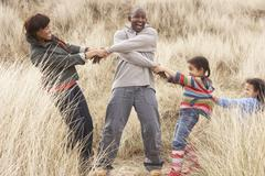family having fun in sand dunes - stock photo