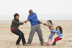 family having fun on winter beach - stock photo
