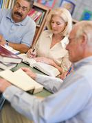 Three people sitting in library with books and notepads (selective focus) - stock photo