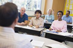 Adult students in class with teacher (selective focus) Stock Photos