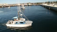 Fishing boat returns to harbor in Monterey California Stock Footage