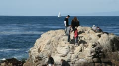 Rocky ocean shore with sightseers and sailboat Stock Footage