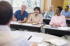 Adult students in class with teacher (selective focus) - stock photo