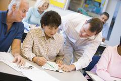 Teacher in class helping adult students (selective focus) - stock photo