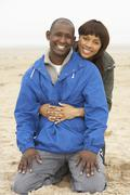 Young couple relaxing on winter beach holiday Stock Photos