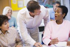 Adult students in class with teacher helping one (selective focus) - stock photo