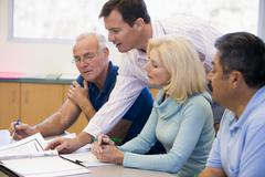 Adult students in class with teacher helping (selective focus) - stock photo