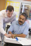 Adult student in class with teacher helping him - stock photo
