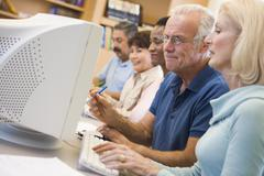 Five people at computer terminals in library (depth of field) Stock Photos