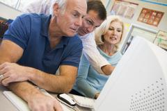 Three people at computer terminal Stock Photos