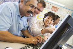 Teacher helping adult students at computer terminals - stock photo