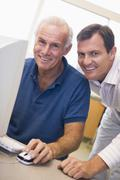 Two men at computer smiling (high key) Stock Photos
