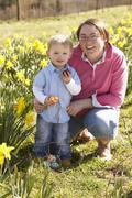 mother and son on easter egg hunt in daffodil field - stock photo