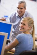 Teacher with female student in computer class - stock photo