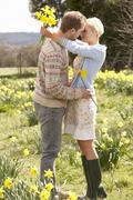Romantic couple walking amongst spring daffodils Stock Photos