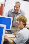 Teacher with male student in computer class - stock photo