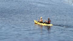 Two fit kayakers paddle across water Stock Footage