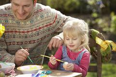 father and daughter decorating easter eggs on table outdoors - stock photo