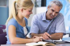 Teacher giving personal instruction to female student - stock photo