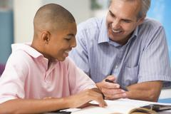 Teacher giving personal instruction to male student - stock photo