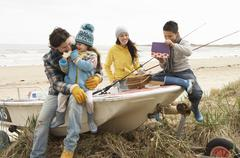 Family group sitting on boat with fishing rod on winter beach Stock Photos