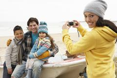 Stock Photo of mother taking family photograph on winter beach