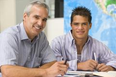 Teacher giving personal instruction to male student Stock Photos