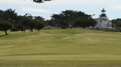 Lighthouse an American flag on golf course Stock Footage