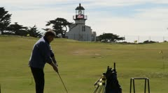 Man hits golf ball with lighthouse an American flag in distance Stock Footage