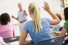 Students answering questions in math class with teacher - stock photo