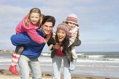 Family walking along winter beach Stock Photos